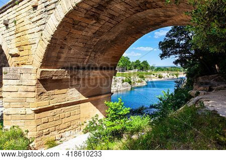The perfectly preserved arch of the bridge - aqueduct. The Pont du Gard is the tallest Roman aqueduct. Interesting trip to France. The shallow Gardon River. Bright sunny day
