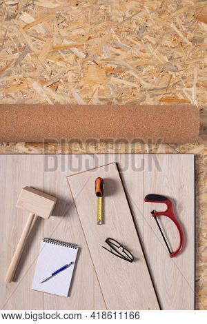Laminate floor on osb wood background texture and tools. Wooden laminate floor plank with copy space