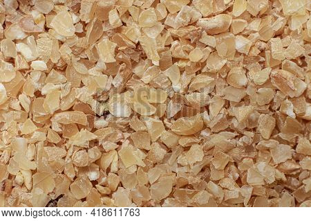 Macro Photo Of Finely Ground Brown Wheat Groats For Russian Porridge Made From Durum Wheat. Top View