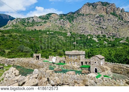 Miniature Model Of The Medieval Fortress Fune Against The Background Of Mountains, In The Place Wher