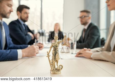 Focus on golden Themis with scales of justice and sward placed on lawyers table, colleagues sitting across from each other in background