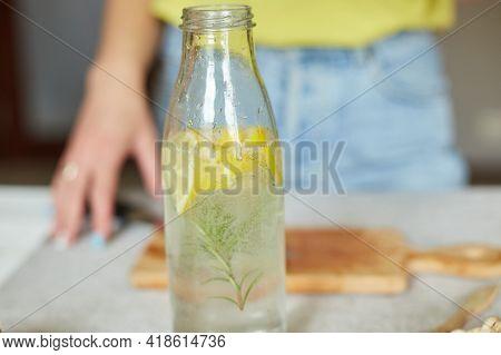 Female Hand Put Lemon In Glass Bottle, Making Detox Healthy Water With Lemon And Rosemary