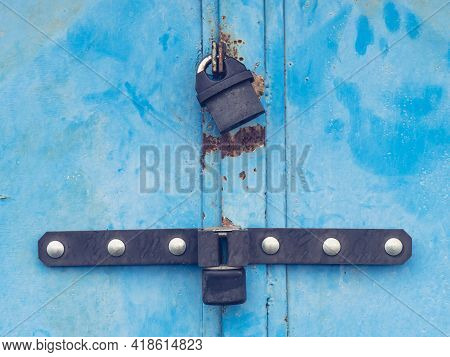 Padlock Housing On Massive Latch. Locked Garage Double Wings Door In Blue Light Weathered Paint
