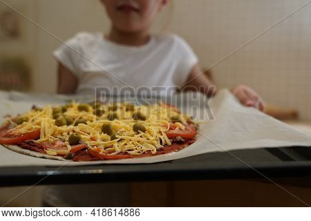 The Girl Holds On A Baking Sheet Prepared For Baking Healthy Gluten-free Pizza With Beef. Gluten-fre