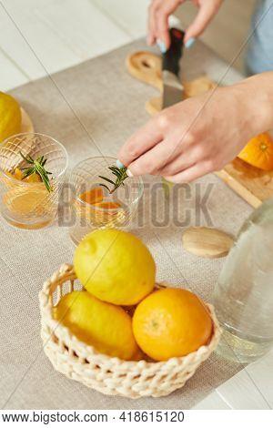 Female Hand Put Rosemary In Glasses, Making Fresh Lemonade