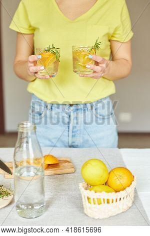 Female Woman Hand Hold Two Glasses Of Citrus Orange And Rosemary Fresh Lemonade
