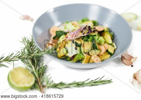Close Up Of Appetizing Salad With Tasty Juicy Shrimps And Zucchini, Garlic On White Background. Conc