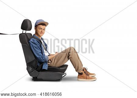 Male teenager sitting in a carseat with a seatbelt isolated on white background