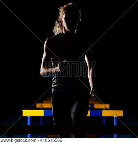 Silhouette Of Young Woman Training With Hurdles