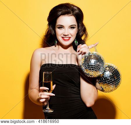 luxury, nightlife, party concept - beautiful woman in evening dress with white wine and disco ball