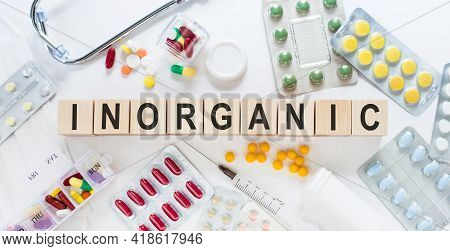 Inorganic Medicine Word On Wooden Blocks On A Desk. Medical Concept With Pills, Vitamins, Stethoscop