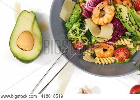 Top View Close Up Of Healthy And Appetizing Pasta With Shrimps, Tomatoes, Avocado And Herbs On White