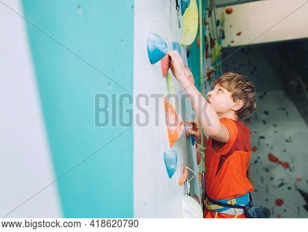 Smiling Teenager Boy At Indoor Climbing Wall Hall. The Boy Is Climbing Using A Top Rope And Climbing
