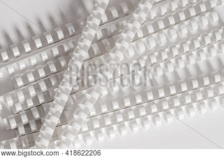 Pile Of Plastic Binding Springs For Connectionv Papers, Lying Down On White Background. Copy Space,