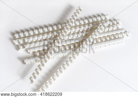 Pile Of Plastic Binding Springs For Connectionv Papers, Lying Down On White Background. Copy Space.