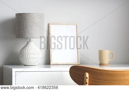 Empty Wooden Frame Mockup On Table With Lamp And Cup Of Coffee. Elegant Feminine Workspace. Scandina