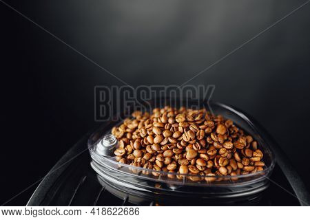 coffee beans in coffeemaker bean container, copy-space background
