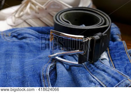 Blue Jeans With Leather Black Belt And Metal Silver-colored Buckle Close-up Across White Sneakers. M