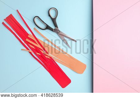Two Stripes Of Kinesiology Tape For Athletes And Scissors On Pink Blue Background, Top View. Copy Sp