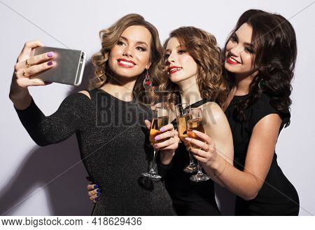 Three fashionable young women dressed in black cocktail dresses are singing with a microphone
