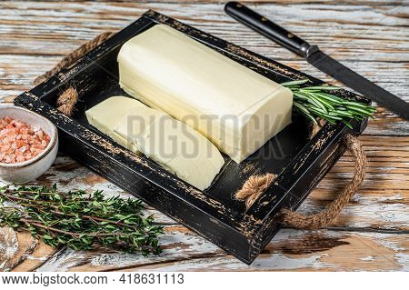 Butter Margarine Block In A Wooden Tray With Herbs. White Wooden Background. Top View