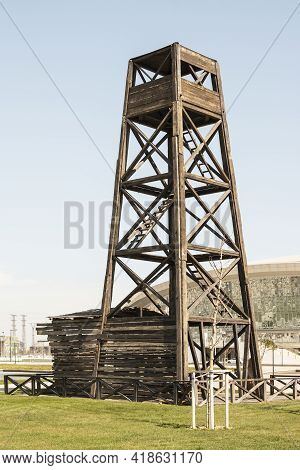 The method of oil production in the early 20th century. Wooden drilling rig. Flammable production.