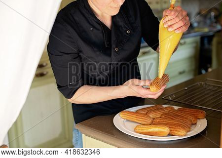 French Dessert Eclair. The Pastry Chef Fills The Eclairs With Creams. Pastry Custard Cakes With Crea