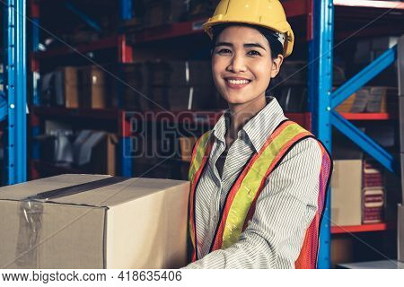 Portrait Of Young Asian Woman Warehouse Worker Smiling In The Storehouse . Logistics , Supply Chain