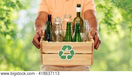 recycling, waste sorting and sustainability concept - close up of african american young man holding wooden box with glass bottles and jars over green natural background