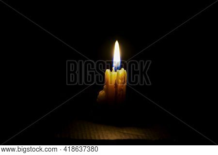Stock Photo Of Small White Color Candle Burning On Dark Background. Focus On Candle, Copy Space.