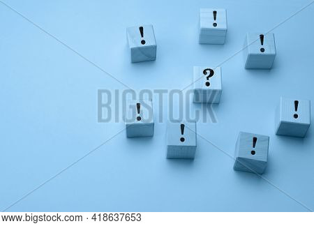 Wooden Cubes With Exclamation Marks And A Question Mark In The Middle On A Light Blue Background. Qu