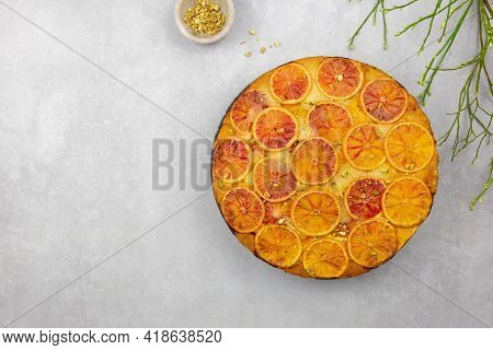 Upside Down Blood Orange And Polenta Cake With Pistachio Nut On Gray Concrete Background. Homemade C