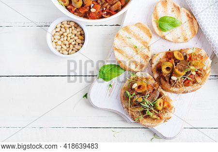 Traditional Italian Caponata And Toast On A Wooden White Table. Sicilian Caponata. Top View, Above,