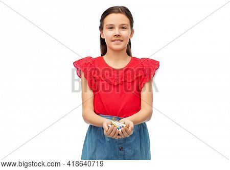 recycling, environment and ecology concept - smiling girl holding pile of alkaline batteries over white background