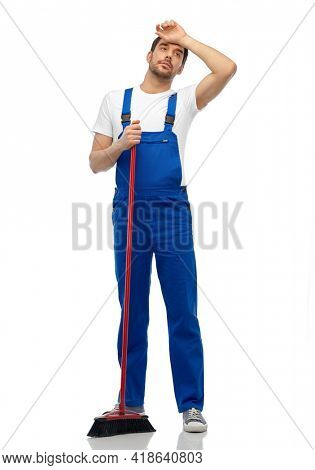 profession, service and people concept - tired male worker or cleaner in overall cleaning floor with broom over white background