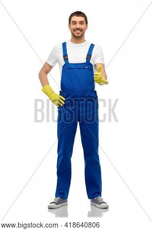 profession, cleaning service and people concept - happy smiling male worker or cleaner in overall and gloves showing thumbs up over white background