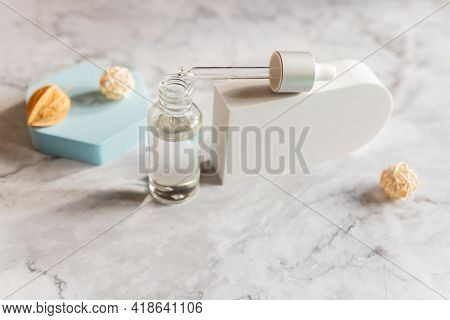 Serum Or Essential Oil In Transparent, Blue Glass Bottle With Pipette, Geometric Shapes And Dried Fl