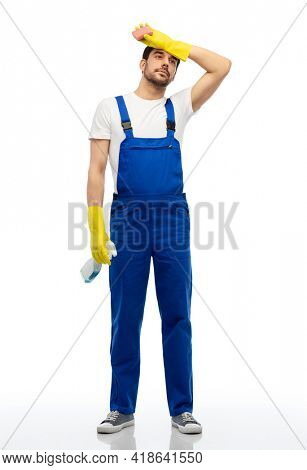 profession, cleaning service and people - tired male worker or cleaner in overal and gloves with sponge and detergent over white background