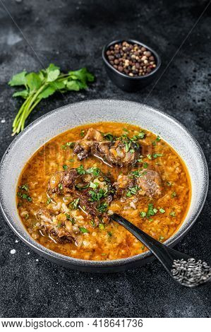 Lamb Soup Kharcho With Mutton Meat, Rice, Tomatoes And In A Bowl. Black Background. Top View