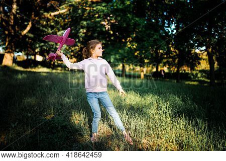 Little Girl Launches A Toy Plane Into The Air In The Park Outdoor. Child Launches A Toy Plane. Beaut