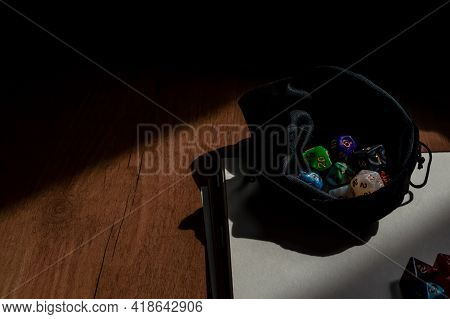 Image Of A Dice Bag Filled With Colorful Rpg Game Dice In The Sun On A Note Book