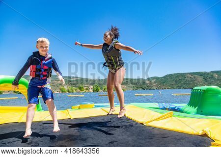 Two happy diverse kids jumping and playing on a inflatable water bounce house on a lake. Jumping on a inflatable trampoline on a summer day is super fun!