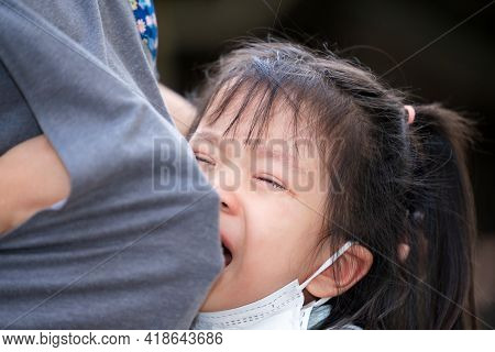 Soft Focus. Cute Asian Kid Is Crying And Regret Nestle On Her Mother's Belly. Mother Used Her Clothe