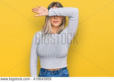 Beautiful blonde woman wearing casual clothes covering eyes with arm, looking serious and sad. sightless, hiding and rejection concept