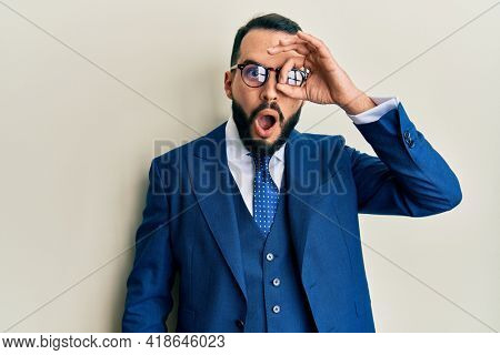 Young man with beard wearing business suit and tie doing ok gesture shocked with surprised face, eye looking through fingers. unbelieving expression.