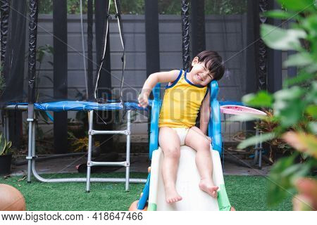 Asian Boy Plays Small Slide In Front Yard House. Child Smile Sweet. Children Is Wearing Yellow Sport