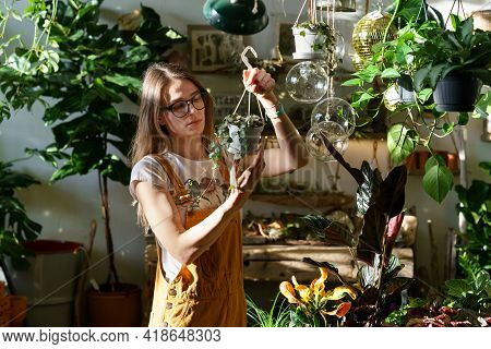 Busy Gardener, Small Business Owner Florist Female In Plant Store Work With Potted Houseplants Over