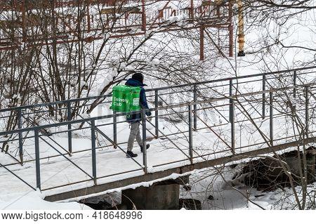 Petrozavodsk, Russia - 12 April 2021. A Foot Courier Walks Across A Bridge Over A Frozen River