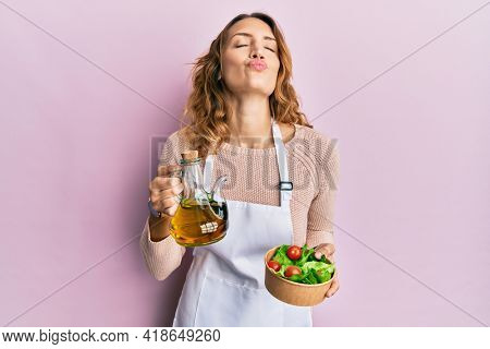 Young caucasian woman wearing apron holding olive oil can and salad looking at the camera blowing a kiss being lovely and sexy. love expression.