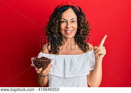 Middle age hispanic woman holding bowl with raisins smiling happy pointing with hand and finger to the side